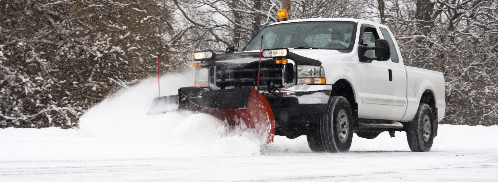 Man in pickup truck plowing road during snow storm